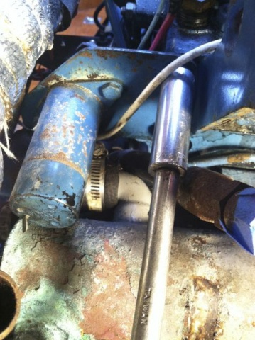 Removing the stop solenoid to reach the hose clamp hidden behind.